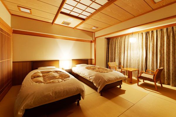 部屋の明かりがついているベッドのある客室(和室)